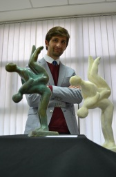 """The artist poses with the sculpture """"Twins"""" in bronze and plaster"""